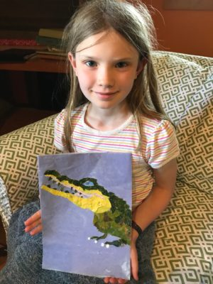 A young girl holding up a completed nature collage of an alligator.